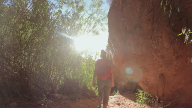 Woman hiking in a canyon with poison ivy