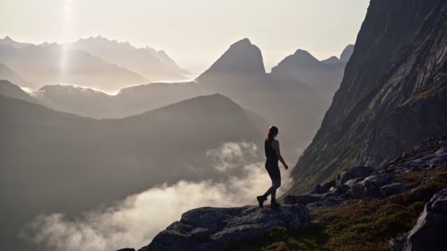 Woman hiking  in mountains  on Senja island in fog