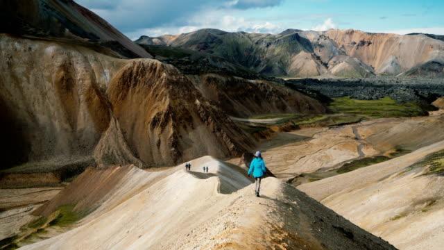stockvideo's en b-roll-footage met vrouw wandelen in de buurt van kleurrijke bergen van landmannalaugar in ijsland - geologie