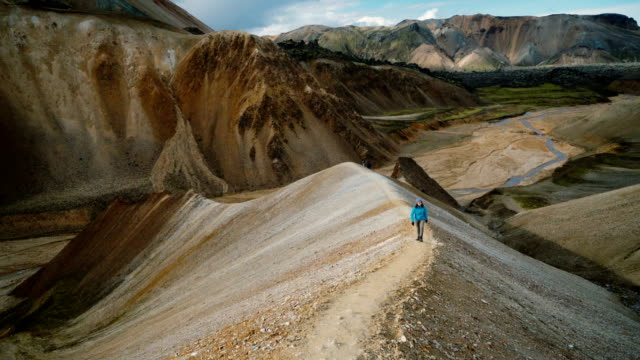 vídeos de stock e filmes b-roll de woman hiking near colorful mountains in landmannalaugar in iceland - geologia