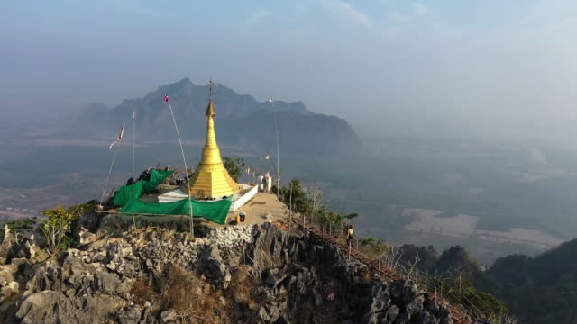 Woman hiking near  golden pagoda in mountains in Hpa An