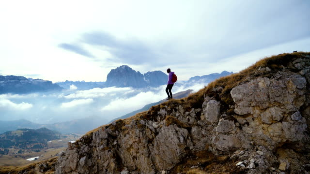 woman hiking near seceda mountain in dolomites - parco nazionale video stock e b–roll