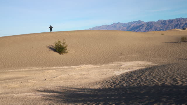 Woman hiking on sand dunes at Mesquite Flats, Death Valley, California. Wawing from the top of the dune.
