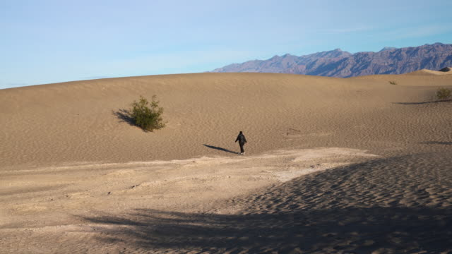 Woman hiking on sand dunes at Mesquite Flats, Death Valley, California.