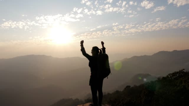 Woman hiking to the Mountain peak and hands up on head celebrating successful , slow motion Woman hiking to the Mountain peak and hands up on head celebrating successful , slow motion 4K(UHD) silhouette people stock videos & royalty-free footage