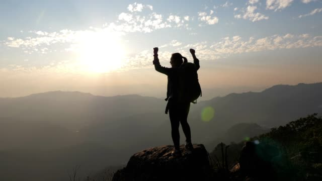 woman hiking to the mountain peak and hands up on head celebrating successful , slow motion - sud est asiatico video stock e b–roll