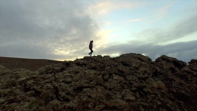 AERIAL: Woman hiking up on the edge of volcanic crater