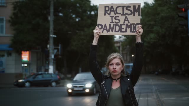 kvinna hipster höjer kartong affisch, inskription rasism är en pandemi. poserar på vägskäl, stadsbildstrafik. slow motion, mörk filmisk - etnicitet bildbanksvideor och videomaterial från bakom kulisserna