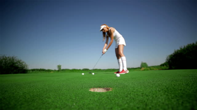 Woman hits three balls at the golf video