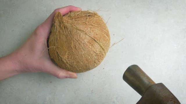 Femme frapper une noix de coco avec un marteau en 4k - Vidéo