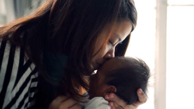 Woman holding a baby and kisses him video