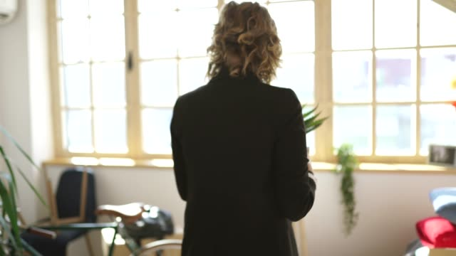 vídeos de stock e filmes b-roll de woman holding a cactus plant for her new apartment - arranjo