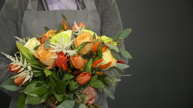 vídeos de stock, filmes e b-roll de uma mulher segurando uma florista em suas mãos um lindo buquê - punhado