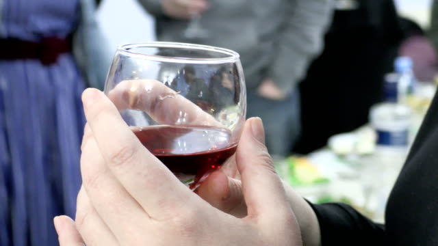 vídeos de stock e filmes b-roll de woman holding a glass of red wine. people clink glasses with drinks at the event. footage 4k, ultra hd, uhd - sideboard