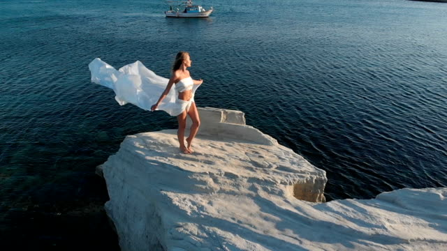 woman holding a large, white fabric in seaside on a rock, an aegean coast - nazionalità russa video stock e b–roll