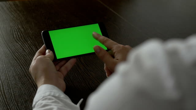 Woman holding a mobile phone with a green screen. For your video content. video