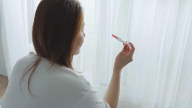 vídeos y material grabado en eventos de stock de mujer que sostiene una prueba de embarazo en las manos - planificación familiar