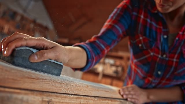 SLO MO Woman holding a sanding sponge and hand sanding a piece of wood