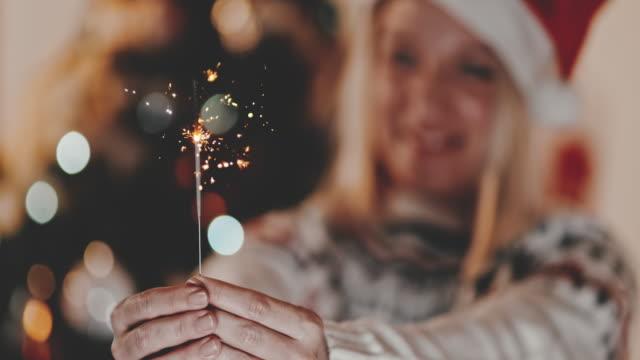 vídeos y material grabado en eventos de stock de slo mo mujer sosteniendo una chispa para navidad - advent