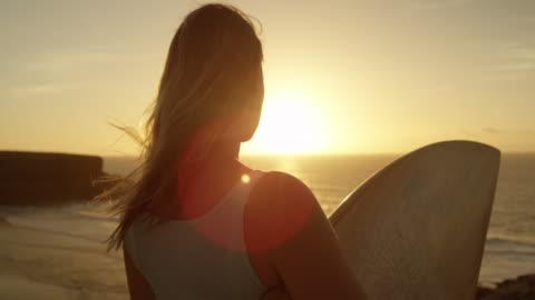 slow motion, primo piano: donna che tiene in mano una tavola da surf, guardando le onde al tramonto. - alba crepuscolo video stock e b–roll