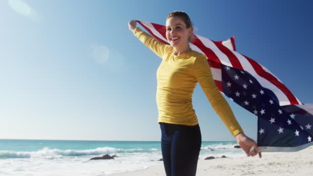 Frau hält amerikanische Flagge am Strand – Video