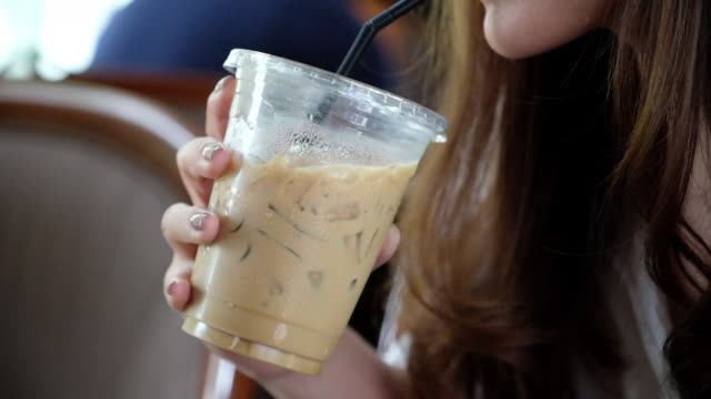 A woman holding and drinking iced coffee by straw in cafe