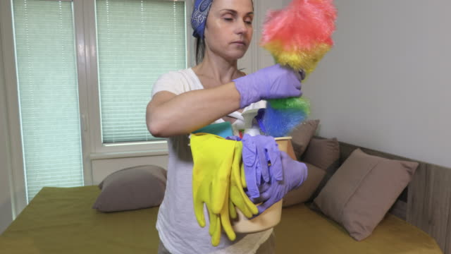 Woman holding and examining plastic bucket full of cleaning products and equipment - vídeo