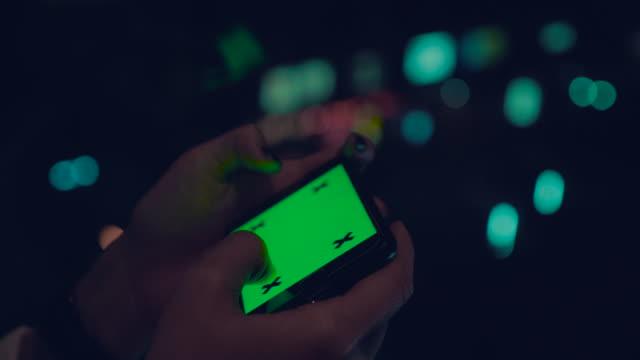 kvinnan håller och med en tom smartphone chroma key - skicka datormeddelande bildbanksvideor och videomaterial från bakom kulisserna