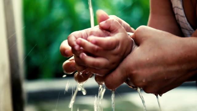 押しながら蛇口の下の娘に手を洗う女性 - 体 洗う点の映像素材/bロール
