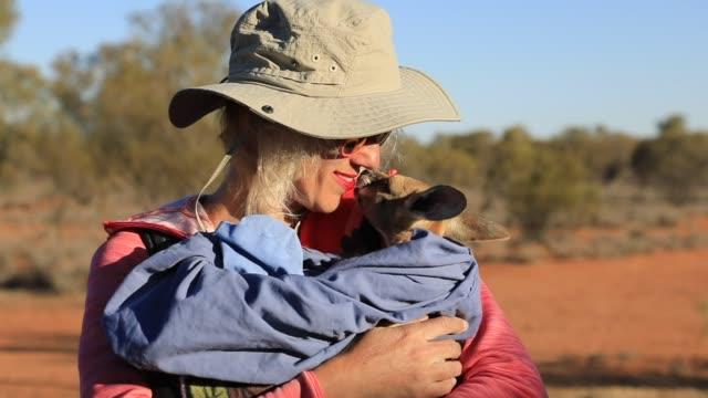 stockvideo's en b-roll-footage met vrouw houden baby kangoeroe - teenager animal
