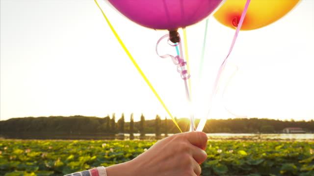 vídeos de stock e filmes b-roll de woman holding balloons. - mulher balões