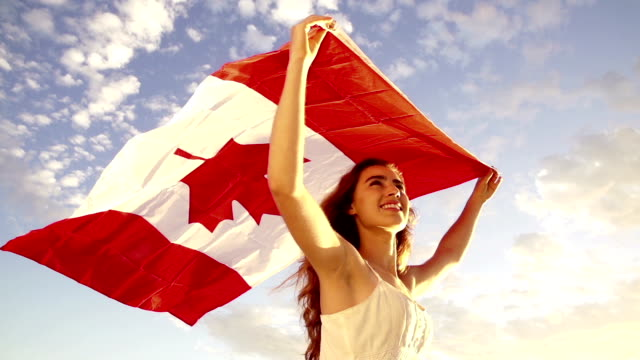 woman holding canadian flag against blue sky - canada flag stock videos & royalty-free footage