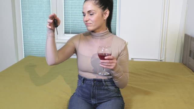 Woman holding car keys and  glass of wine - vídeo