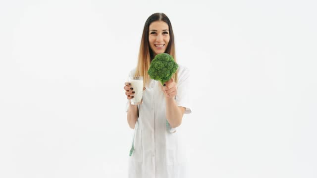 Woman holding cauliflower and galss of milk