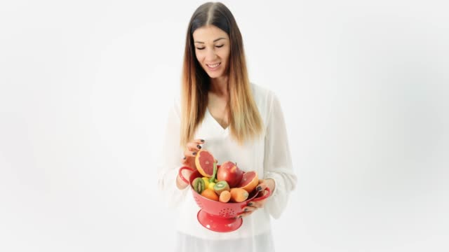 Woman holding colander of organic fruit and vegetables