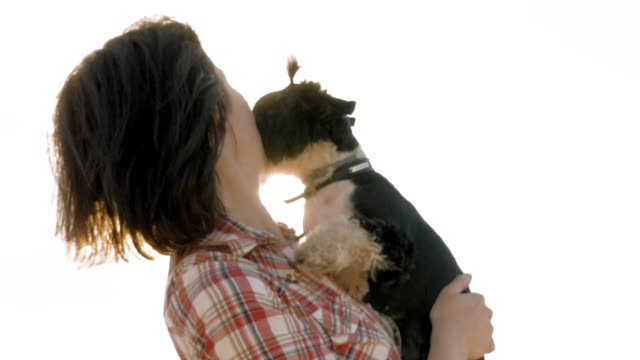 Woman holding dog in hands with backlight sunset video