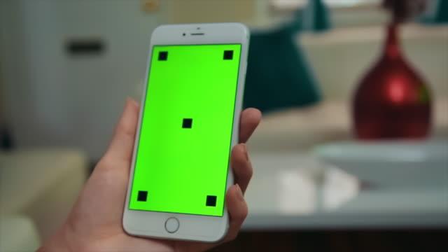 vídeos y material grabado en eventos de stock de mujer sosteniendo el teléfono celular de pantalla verde - seo
