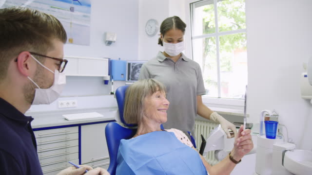 Woman holding hand mirror while talking to dentist