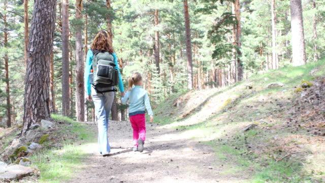 stockvideo's en b-roll-footage met vrouw met hand aan meisje wandelen in het bos - {{asset.href}}