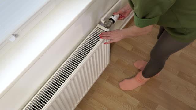 Woman holding hands on heating radiator - vídeo