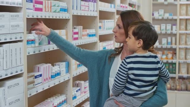 vídeos y material grabado en eventos de stock de ds mujer sosteniendo a su hijo y recoger una botella de medicamento de la estantería en la farmacia - recipiente para las píldoras