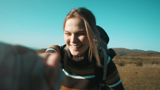 woman holding her man hand on hiking trip - distinguersi dalla massa video stock e b–roll