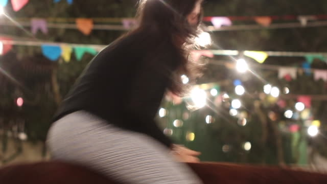 Woman holding herself to mechanical bull. Girl rides electric mechanical bull