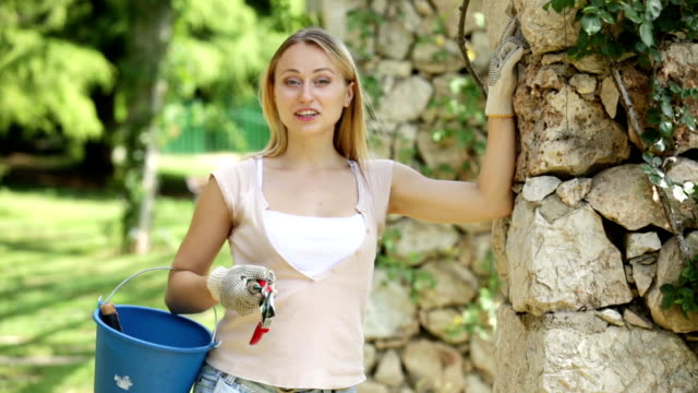 woman holding horticultural tools in garden video
