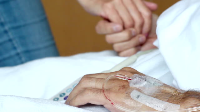 Woman holding husbands hand in a hospital bed with IV in his arms