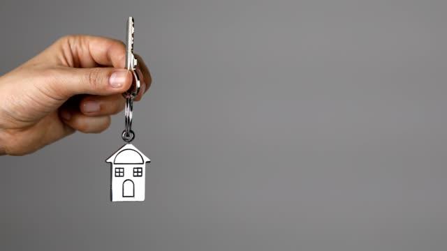 frau hält schlüssel eines neuen hauses auf einem hausförmigen schlüsselanhänger - hausschlüssel stock-videos und b-roll-filmmaterial