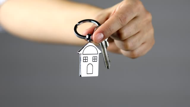 woman holding keys of a new home on a house shaped key ring - key ring stock videos & royalty-free footage