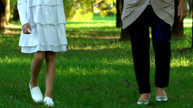 woman holding little girl hand and walking in green park at summer, weekend - nonna e nipote camminare video stock e b–roll