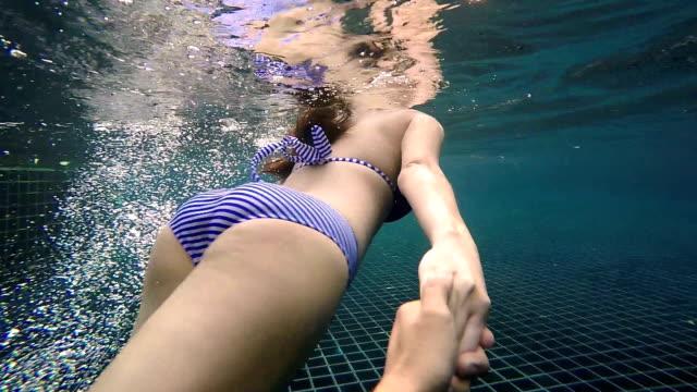 Vrouw die iemands hand en leidt hem onder het water in zwembad video