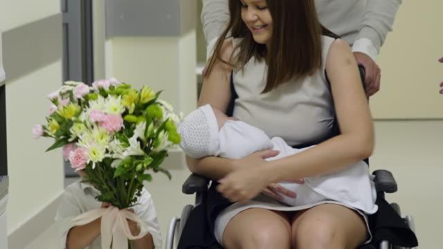 kvinna holding nyfödda baby och lämnar bb med familj - hospital studio bildbanksvideor och videomaterial från bakom kulisserna